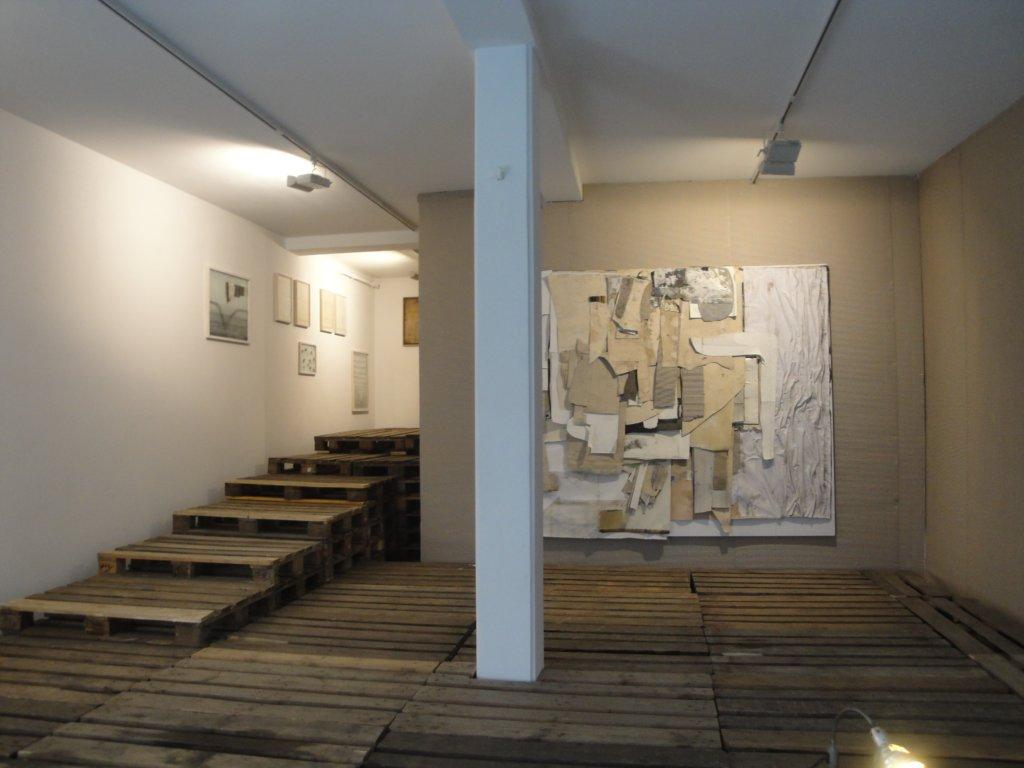 Man sieht die Galerie von innen, dabei ist mit Holzpaletten und Wandverkleidung ein eigener Raum in den eigentlichen Galerieraum gebaut worden.