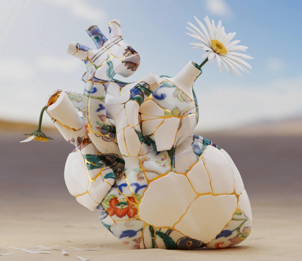 Eine Vase in Form eines Herzens, aus Scherben zusammengesetzt. Darin ein blühendes und ein verblühtes Gänseblümchen