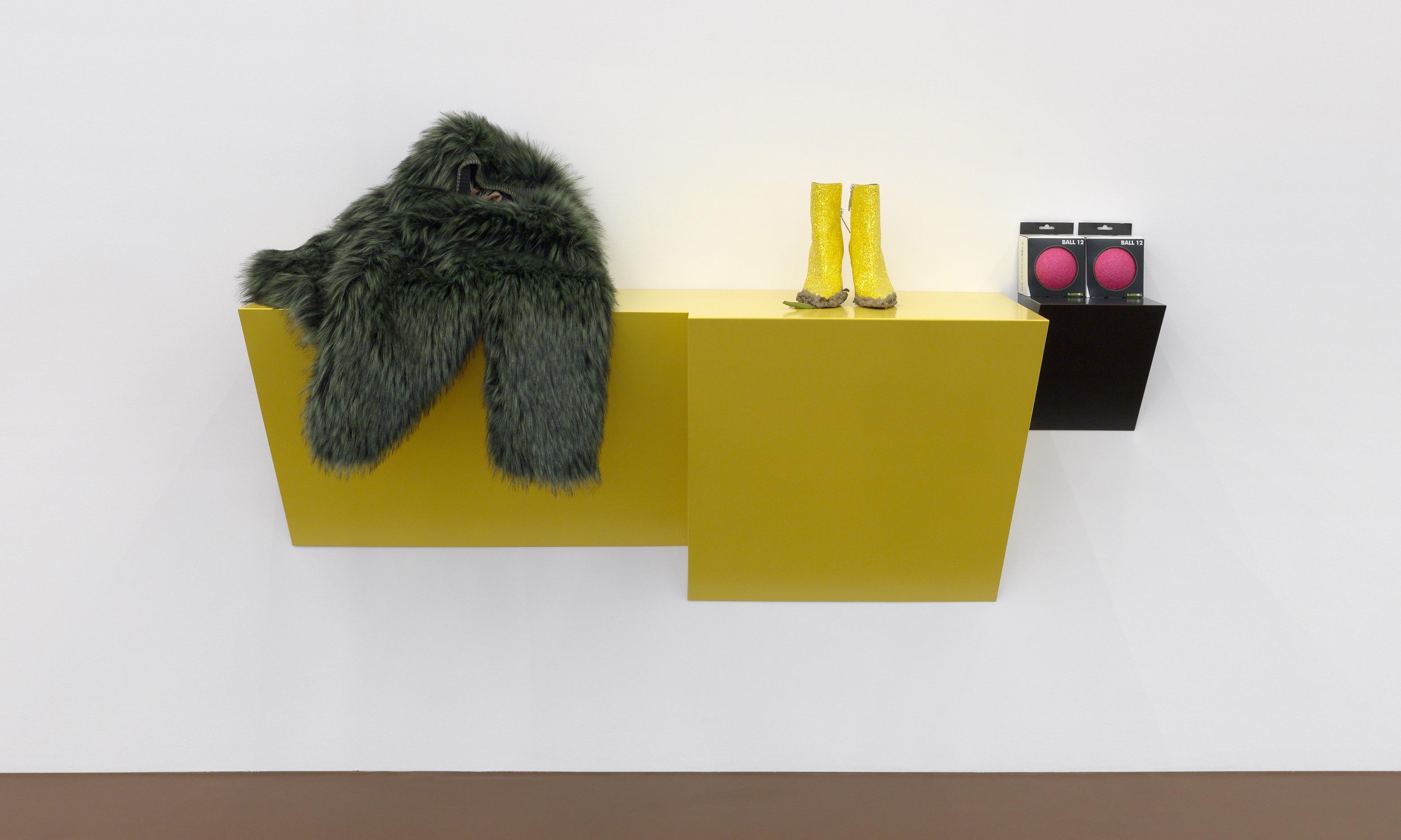 Gelbes Sideboard, darauf eine Felljacke, gelbe Glitzerstiefeletten und zwei Bälle.