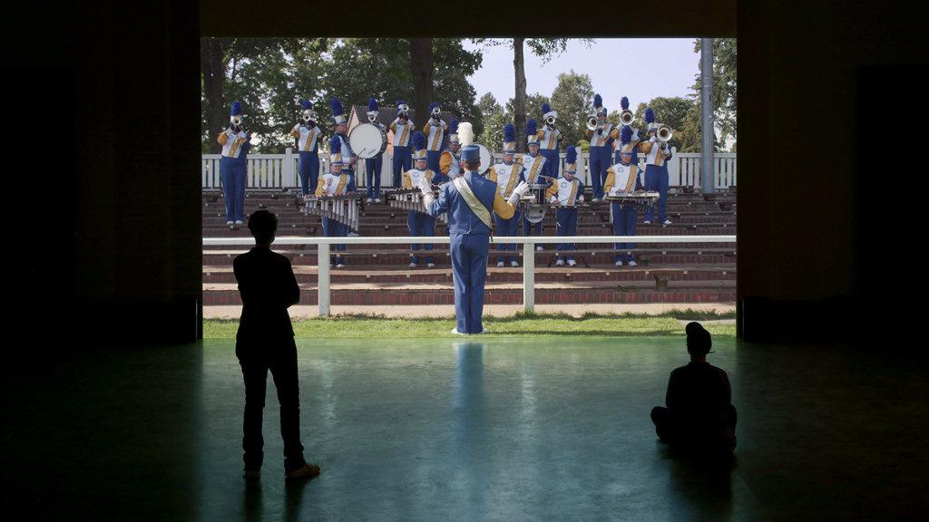 Das Bild zeigt einen dunklen Raum, an dessen Ende eine wandfüllende Leinwand angebracht ist. Die Leinwand zeigt das Bild einer Blaskapelle in Uniformen auf einem Podest. Der Blaskapellen-Dirigent ist aus der Rückenansicht zu sehen. Vor der Leinwand in dem Raum befinden sich zwei Personen, rechts sitzend, links stehend.