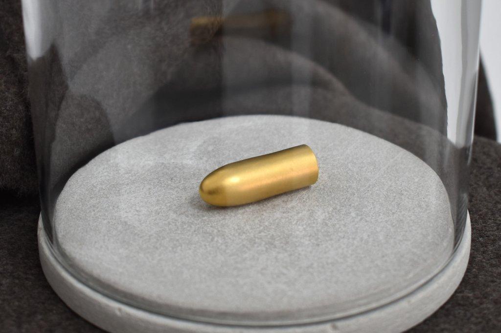Das Bild von Katja Windau zeigt einen kleinen goldenen Gegenstand unter einer Glasglocke, der die Form einer Patrone hat