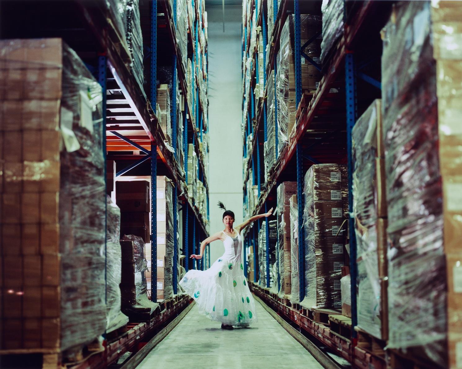 Eine Frau tanzt in langem Kleid und mit Federschmuck im Haar in einer Fabrikhalle.
