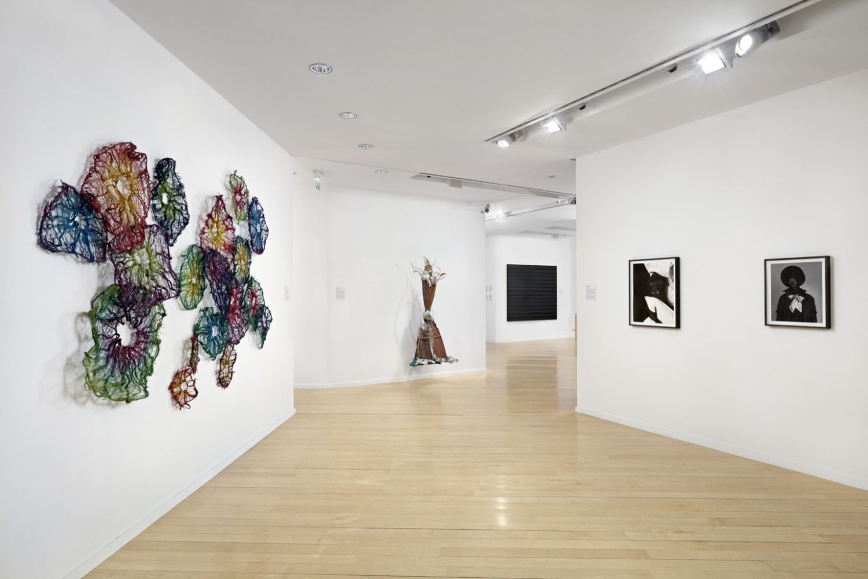 Ausstellunsgansicht 31:Women Daimler Art Collection Weiße Ausstellunsgwände mit Kunstwerken: Fotografien und skulpturale Elemente.