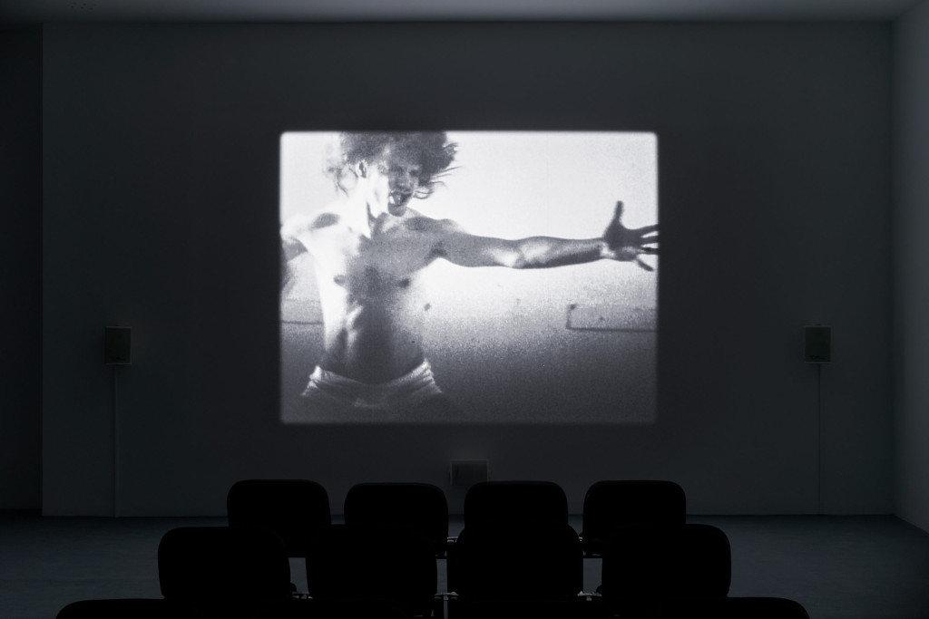Das Bild zeigt einen dunklen Raum an dessen Ende eine Leinwand angebracht ist. Auf der Leinwand ist in schwarz-Weiß ein Mann von der Hüfte aufwärts zu sehen, welcher seinen linken Arm zur rechten Bildseite ausstreckt. Der Gesichtsausdruck des Mannes ist aggressiv oder angespannt, er zeigt seine Zähne und scheint ruckartig den Kopf zu schütteln. Vor der Leinwand im Vordergrund des Bildes sind zwei Stuhlreihen zu sehen. Bei dem Foto handelt es sich um eine Ausstellungsansicht.