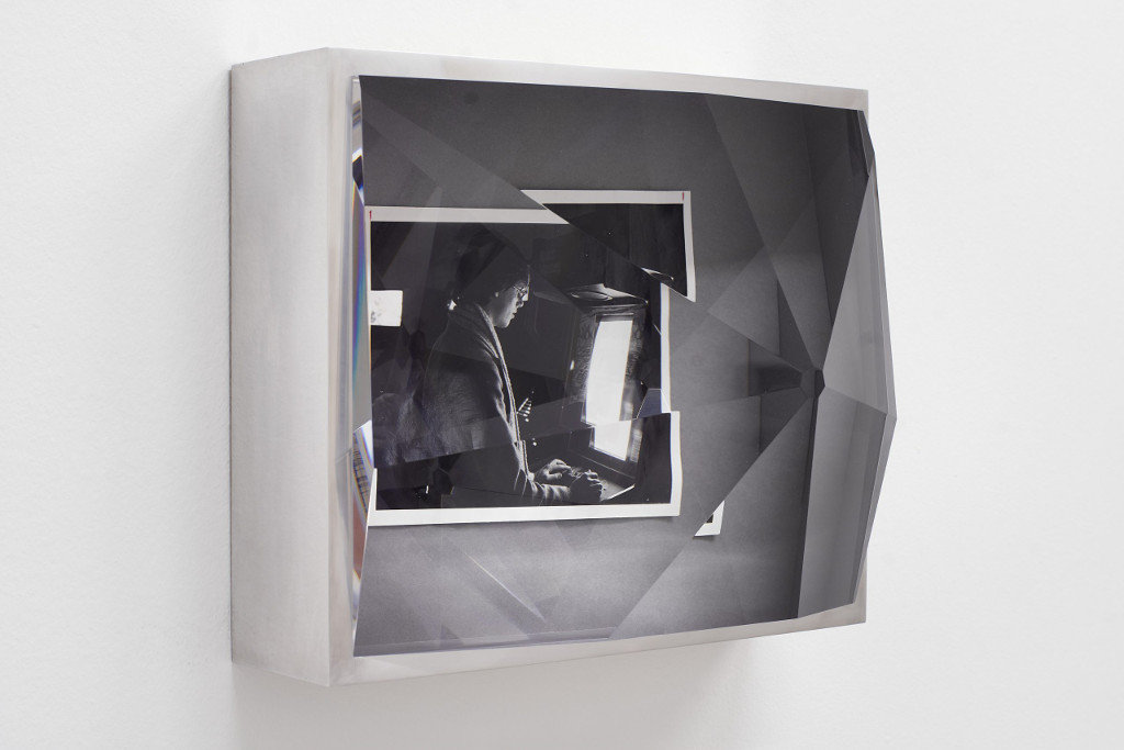 Das Bild zeigt eine Arbeit des Britischen Künstlers Jeremy Shaw. Die Arbeit besteht aus einer schwarz-weiß Fotografie, über welche ein massives Prisma aus Glas gelegt ist. Um Das Bild herum ist ein weißer Rahmen angebracht. Die Fotografie unter dem Prisma zeigt eine Person, die auf einen Bildschirm schaut, jedoch ist der Bildinhalt nicht genau zu erkennen. Die Arbeit hängt an einer Wand, bei dem Bild handelt es sich um eine Installationsansicht.