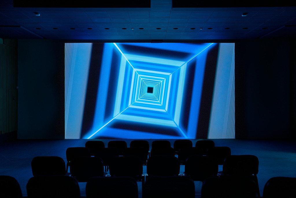 Das Bild zeigt einen dunklen Raum an dessen Ende eine Leinwand angebracht ist. Auf der Leinwand ist eine Art Tunnel aus nach hinten kleiner werdenden Quadraten in einem Neon-Blau zu sehen. Das Gebilde scheint sich zu bewegen. Vor der Leinwand im Vordergrund des Bildes sind mehrere Stuhlreihen zu sehen, bei dem Bild handelt es sich um eine Ausstellungsansicht.