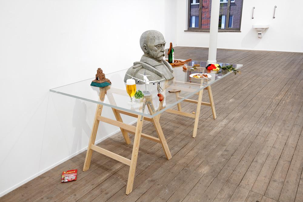 Objekte von Alex Wissel in der Galerie Conradi. Auf einem Glastisch steht unter anderem eine Bismarck-Büste.