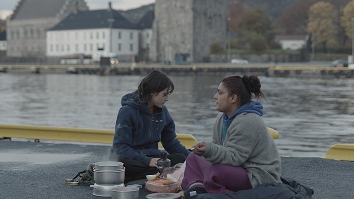Zwei Frauen sitzen am Ufer eines Flusses