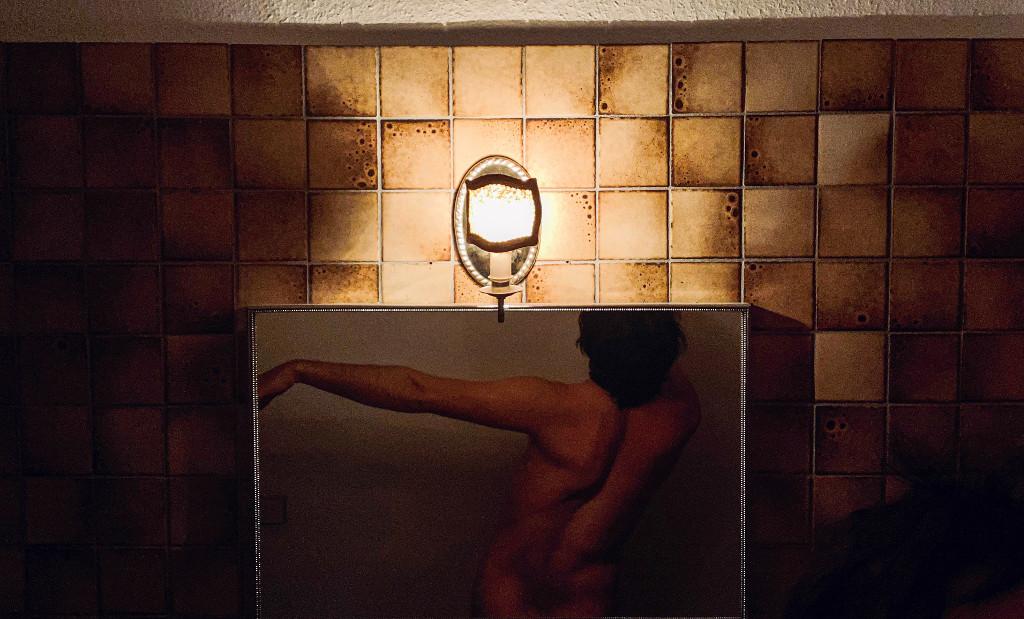 Das Bild zeigt einen männlichen Oberkörper in Rückenansicht. Der Torso scheint in einer Art Kasten zu stecken, welcher vor einer Wand mit braunen Fliesen steht. Über dem Kasten, etwas überhalb des Bildzentrums ist eine Art Lampe angebracht, welche das Bildgeschehen zu beleuchten scheint. Das Medium des Originalwerkes ist durch die Reproduktion nicht genau zu erkennen.