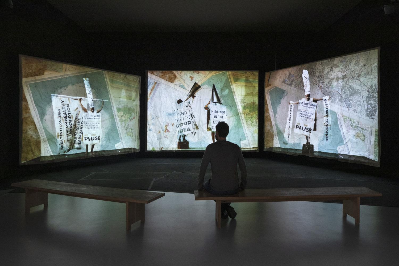 Drei Leinwände sind tryptichonartig angeordnet. Auf allen Flächen ist eine mit Schrifttafeln kostümierte Tänzerin zu sehen