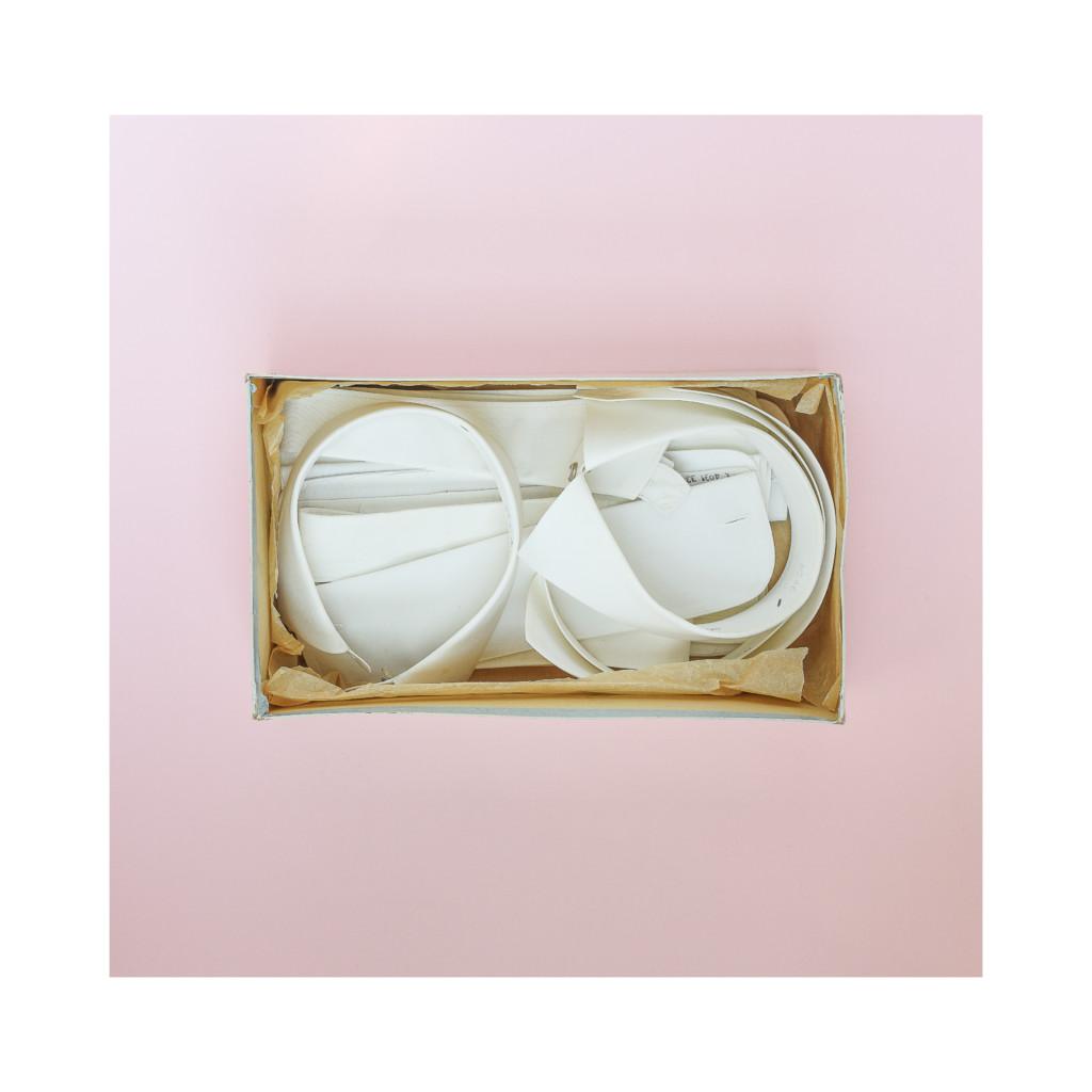 Eine Schachtel mit Hemdkrägen und Aufschlägen vor rosafarbenem Hintergrund.