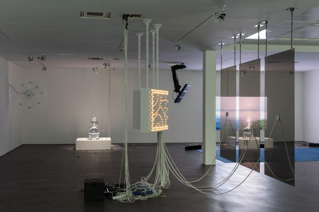 Installationsansicht von Philippe Parreno. Viele Kabel, Licht, ein Film auf einer Leinwand, eine Schneemann-Figur aus Eis, die angeleuchtet wird.