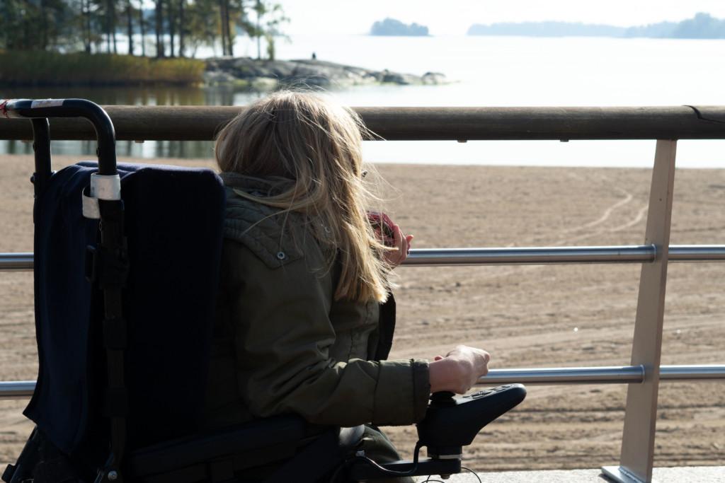 Eine Frau im Rollstuhl, die auf das Wasser und die Natur blickt. Gesicht ist nicht zu erkennen.