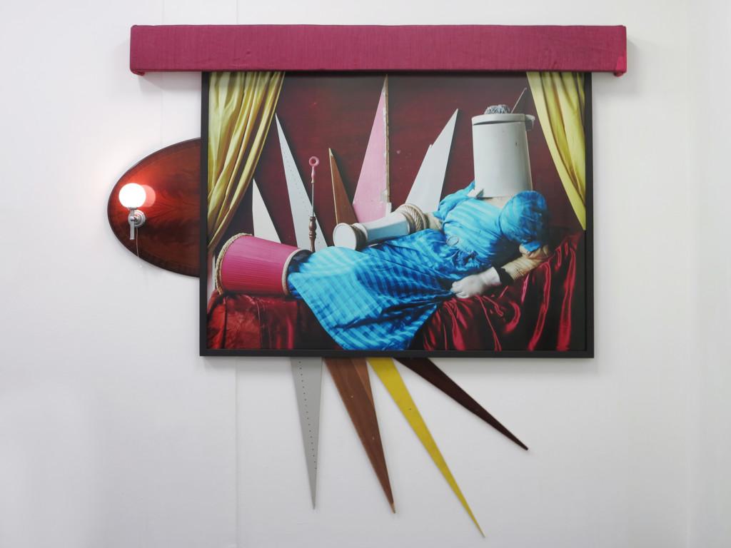 Fotografie mit Darstellung einer liegenden Figur aus allerlei Gegenständen - der Kopf ist ein Mülleimer, der Körper eine blaue Decke und rum um die Figur herum sind rote Vorhänge in der Art einer Renaissance-Venus drapiert.