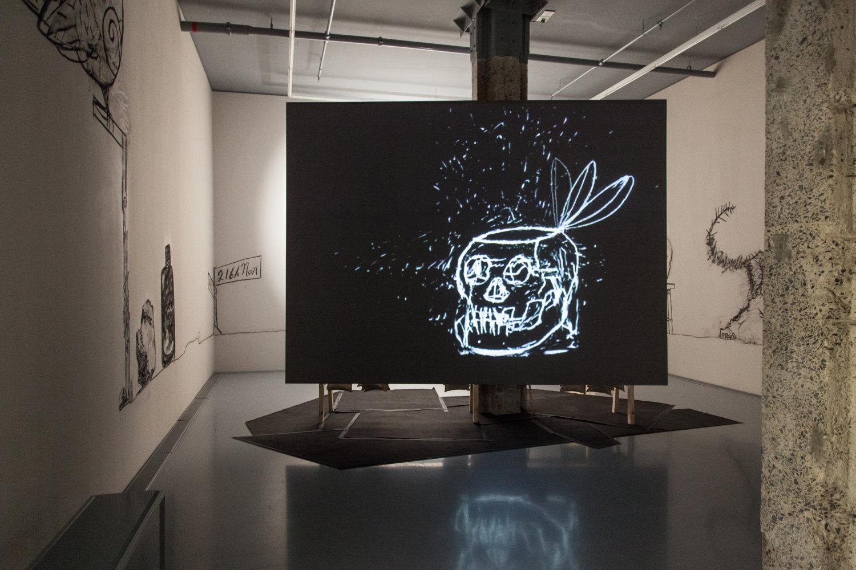 Eine schwarze Leinwand, darauf in weiß die Animation eines Schädels mit geöffneter Schädeldecke