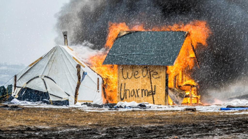 """Im Filmstill aus Cyrill Lachauers """"Cockaigne - I am not sea, I am not land"""" aus dem Jahr 2020 sieht man eine brennende Hütte, auf ihr steht geschrieben: We are unarmed, wir sind nicht bewaffnet."""
