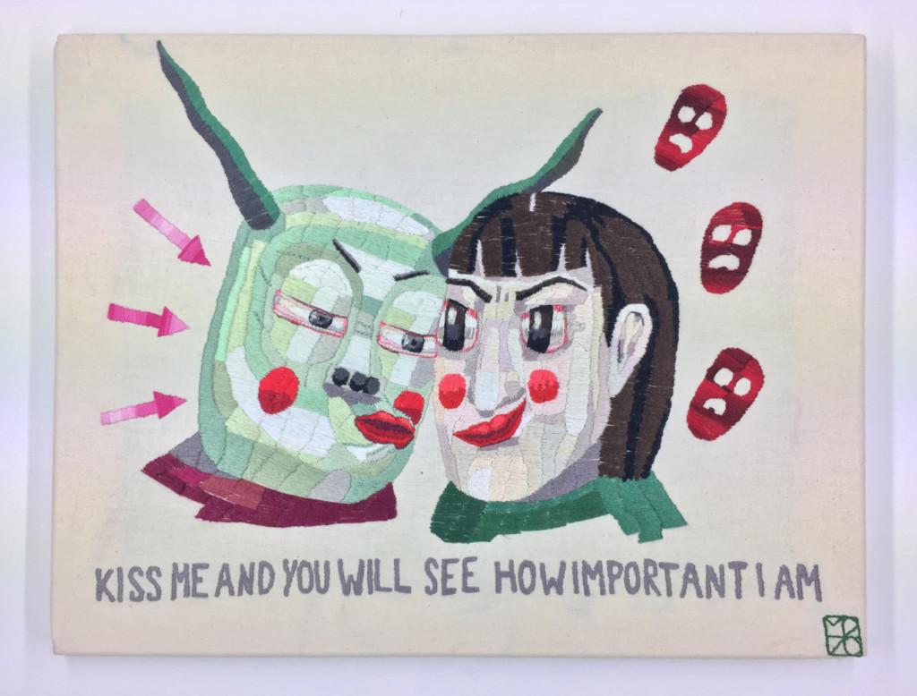 """Eine bestickte Leinwand auf der sich zwei Figuren zum Kuss zueinander lehnen. Eine trägt monströse Züge. Darunter das Sylvia Plath Zitat """"Kiss me and you will see how important I am"""""""