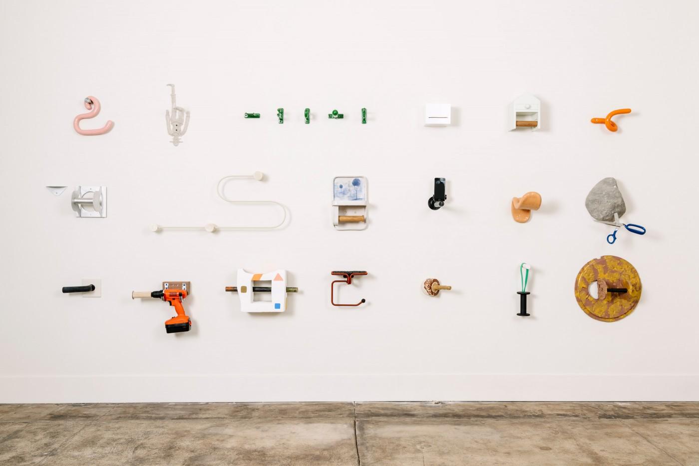 Eine weiße Ausstellungswand mit vielen verschiedenen Toilettenpapierhalterungen.
