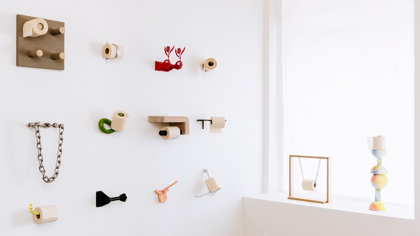 Eckansicht einer Ausstellung mit vielen verschiedenen Toilettenpapierhaltern, die mit Klopapier ausgestattet sind.