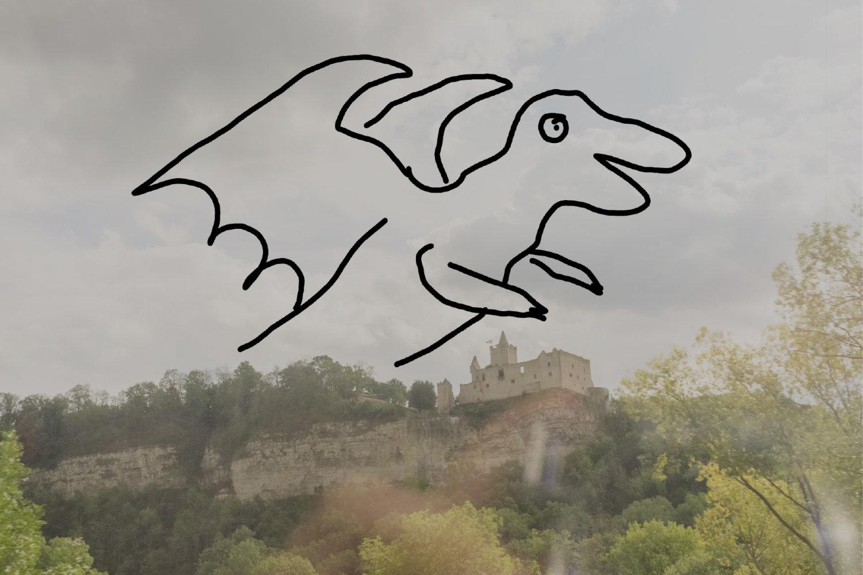 Eine Drachenzeichnung von Sebastian Jung auf einem Handyfoto, das eine Burg auf einem Hügel zeigt.