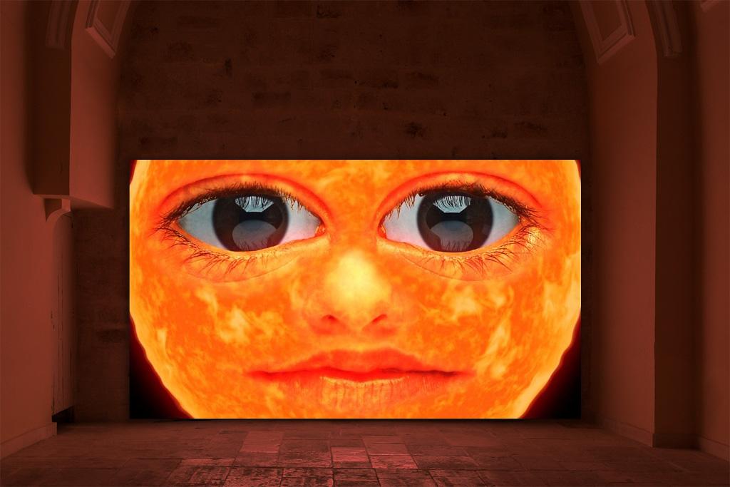 Das Bild zeigt eine rechteckige Fläche in einem kumpelförmigen Innenraum. Bei der Fläche handelt es sich um einen Bildschirm, auf welchem ein Video gezeigt wird. Bildausschnitt ist ein großes Animations-Gesicht, welches von einer Sonne oder einer Lava-artigen Struktur zu kommen schein. Der Gesichtsausdruck ist freundlich-neutral. Der Innenraum ist lediglich ausschnitthaft zu sehen.
