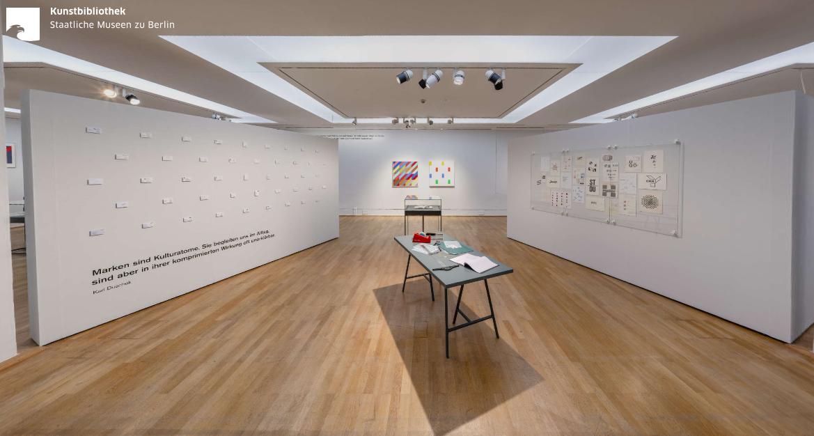 Einblick in einen weißen Ausstellungsraum mit Stellwänden an den Seiten.