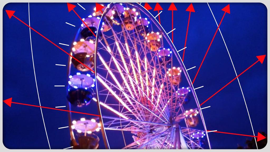 Das Bild zeigt den oberen Teil eines beleuchteten Riesenrades vor einem dunkelblauen Himmel. Die Farben der Lichter am Riesenrad gehen von Blau ins Violett. Aus den Streben des Rades heraus sind digital rote Pfeile in das Bild gezeichnet, welche zu den Rändern des Bildes heraus zeigen.