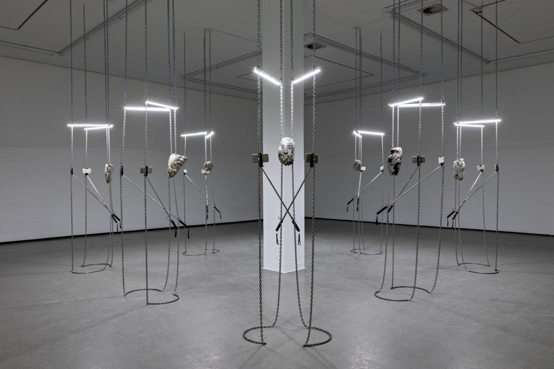 """Man sieht eine Installation aus von der Decke hängenden Ketten, an denen jeweils verikal zwei weiße Neonröhren und darunter Einzelteile aus Metall angebracht sind, die den Eindruck eines """"skelett- oder strichmännchenartigen"""" Körpers erwecken."""
