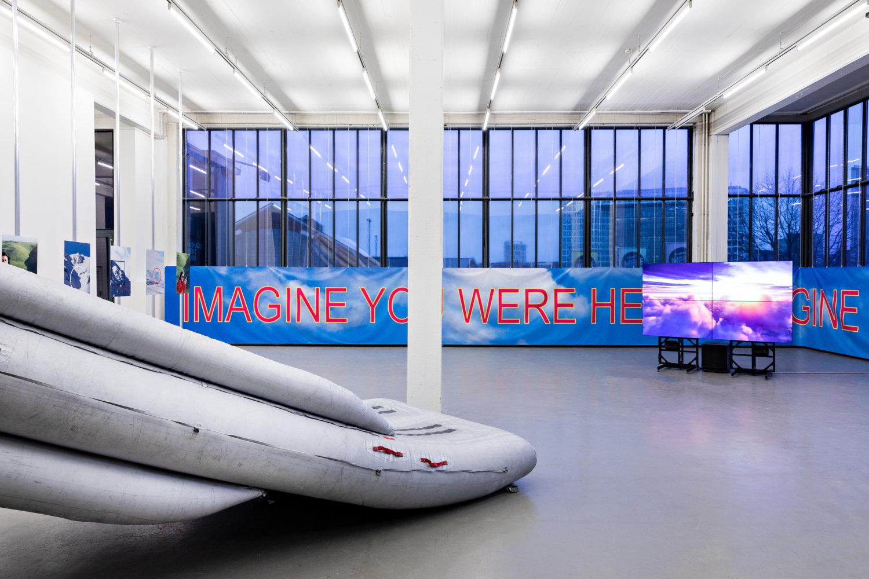 Man sieht eine Installation aus weißen Booten und einem blaue Banner mit roter Schrift, auf der es heißt: Imagine you were here.