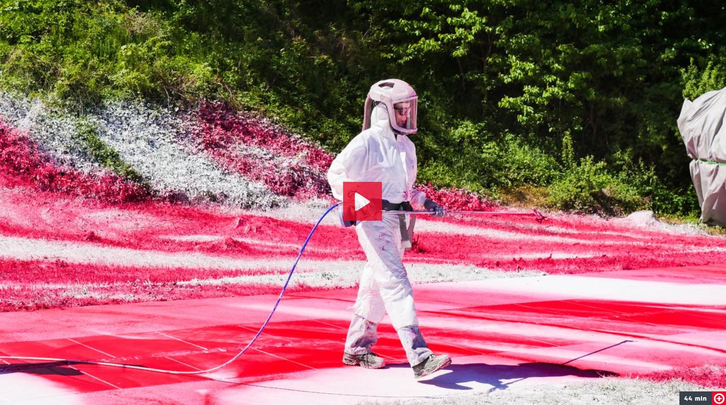 Künstlerin Katharina Grosse in einem Schutzanzug und gerade dabei, Weg und Wiese mit bunter Farbe zu besprühen.