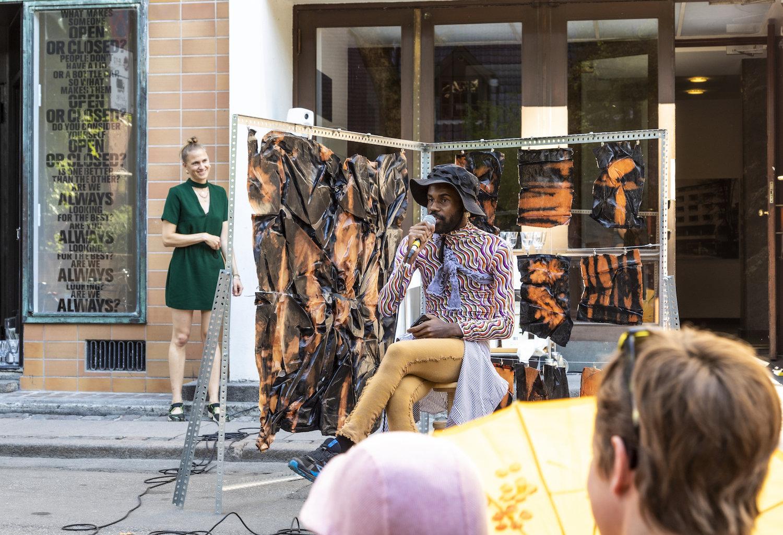 Man sieht eine Performance des Künstler Ndayé Kouagou, er sitzt in der Mitte.