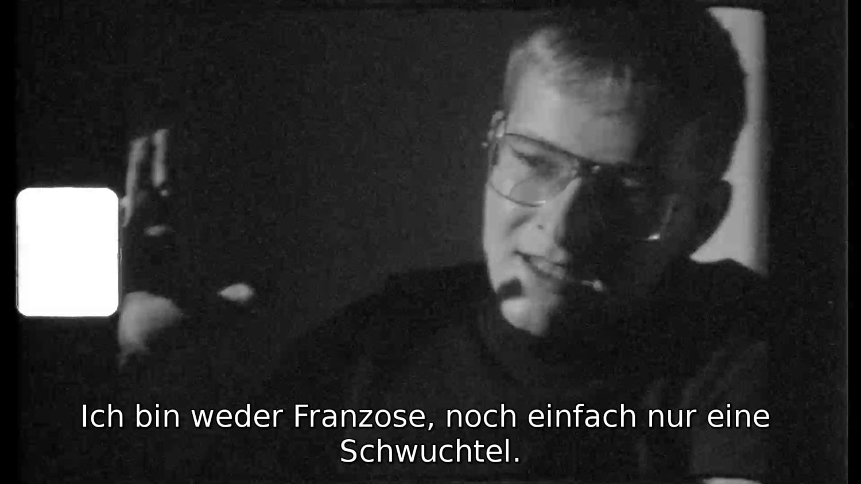 Videoarbeit von Julian Volz. Ein Mann spricht, Bild in Schwarzweiß.