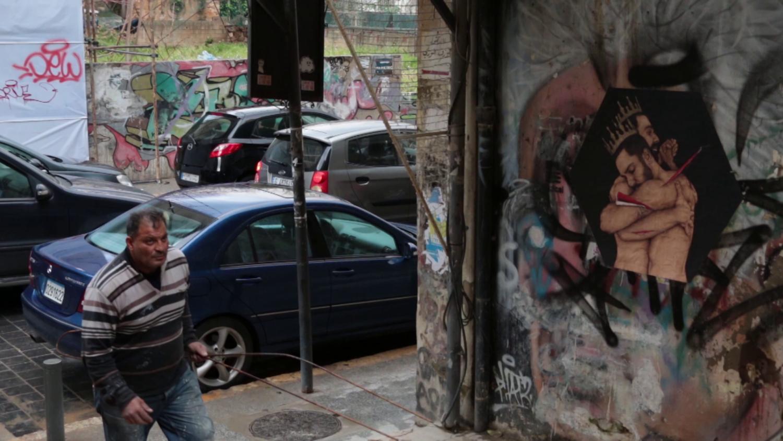 Ein Mann geht in eine Seitenstraße. An der Wand ist eine Zeichnung von zwei Männern mit freiem Oberkörper, die einander im Arm halten.