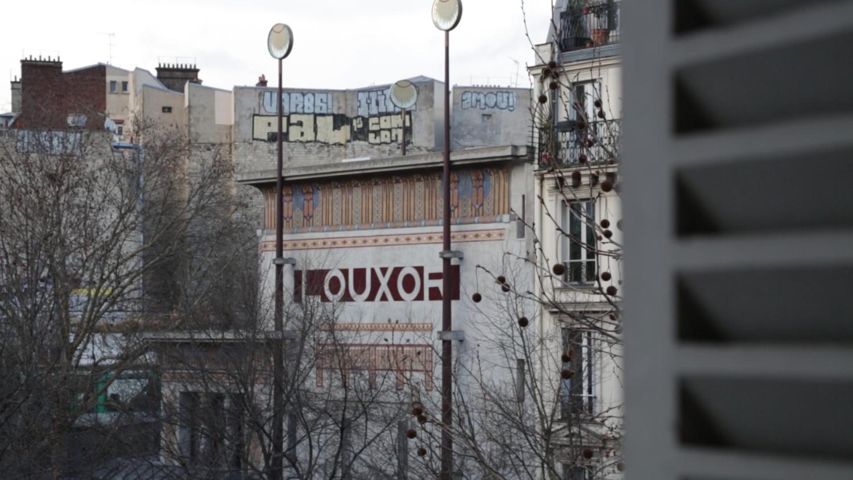 """Videoarbeit von Julian Volz, Gebäude mit """"Mithly"""" Graffiti."""