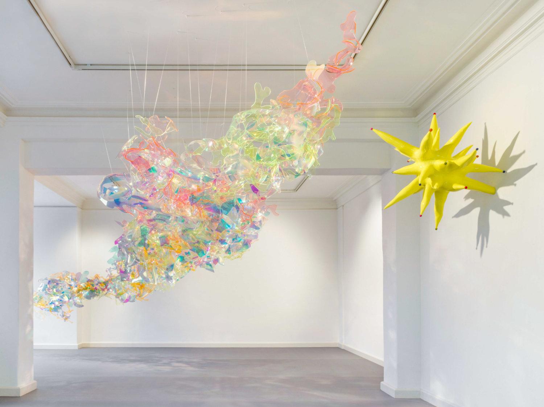 Ein heller Ausstellungsraum mit zwei skulpturalen Kunstwerken. Eines hängt rechts an der Wand, das andere hängt von der Decke und scheint im Raum zu schweben. Es ist an transparenten Schnüren befestigt.