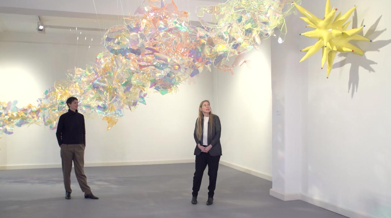 Die Künstlerin Berta Fischer in einem Ausstellungsraum unter ihren Kunstwerken stehend