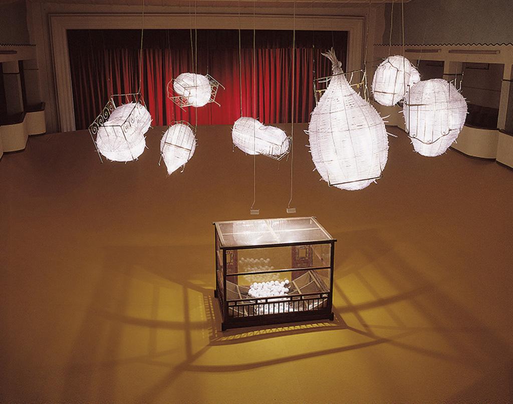 Das Bild zeigt eine künstlerische Installation. Sie scheint sich in einem Theater zu befinden, im Hintergrund des Bildes ist ein roter Vorhang zu sehen. Die Installation besteht aus einem Glaskasten mit einem Holzgestell am Boden. In dem Kasten scheinen kleine weiße Bälle zu liegen. Über dem Kasten hängen Lampion-artige Gebilde, um welche Drahtgerüste angebracht sind. Die Gebilde sind beleuchtet.