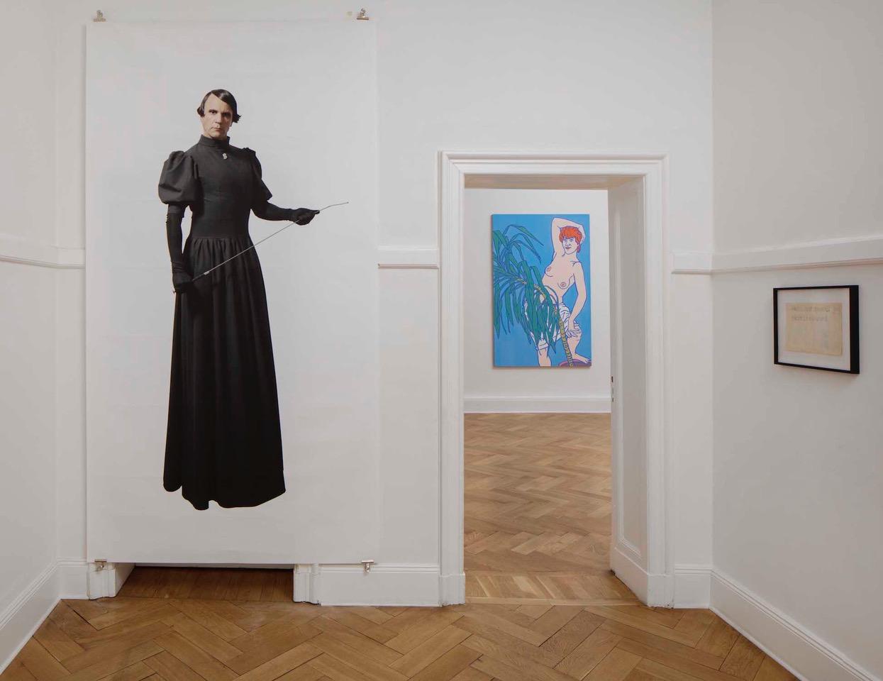 Eingangssituation in einer Berliner Altbauwohnung. Zu sehen ist der Künstler Björn Melhus als Ayn Rand. Im Hintergrund ein Bild von Otto Muehl mit einer Nacktdarstellung einer Frau.