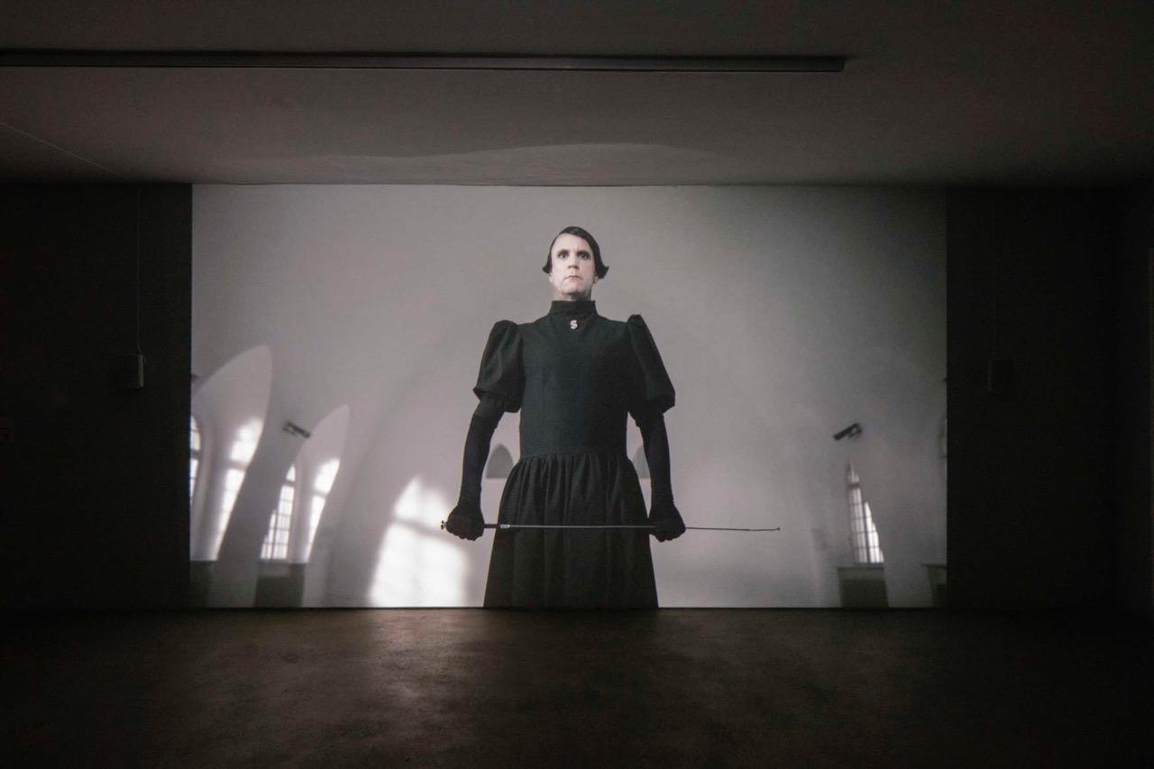 Videoarbeit von Björn Melhus. Man sieht den Künstler verkleidet als Ayn Rand.
