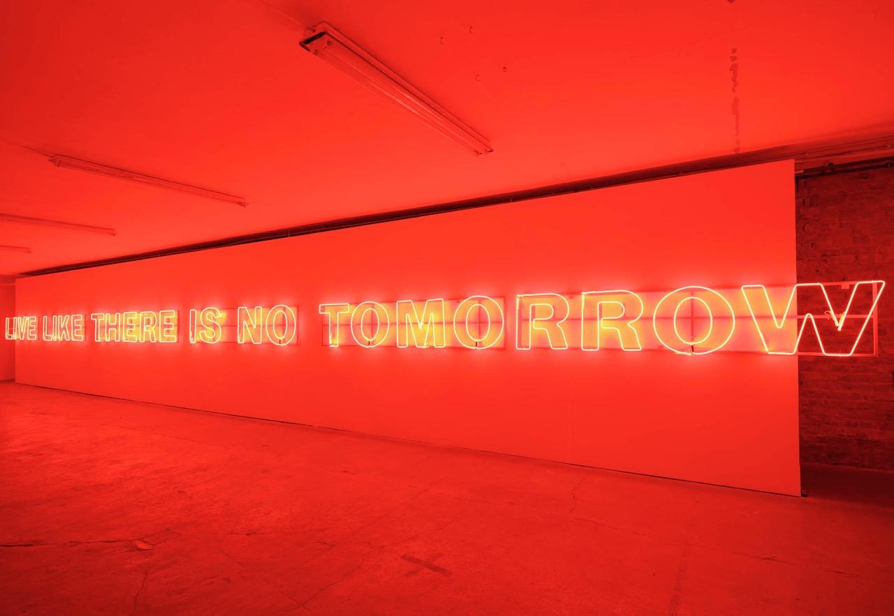 Kellerraum mit Neonröhren an der Wand, die den Raum in rotes Licht tauchen. Dort steht: Live like there is no tomorrow.