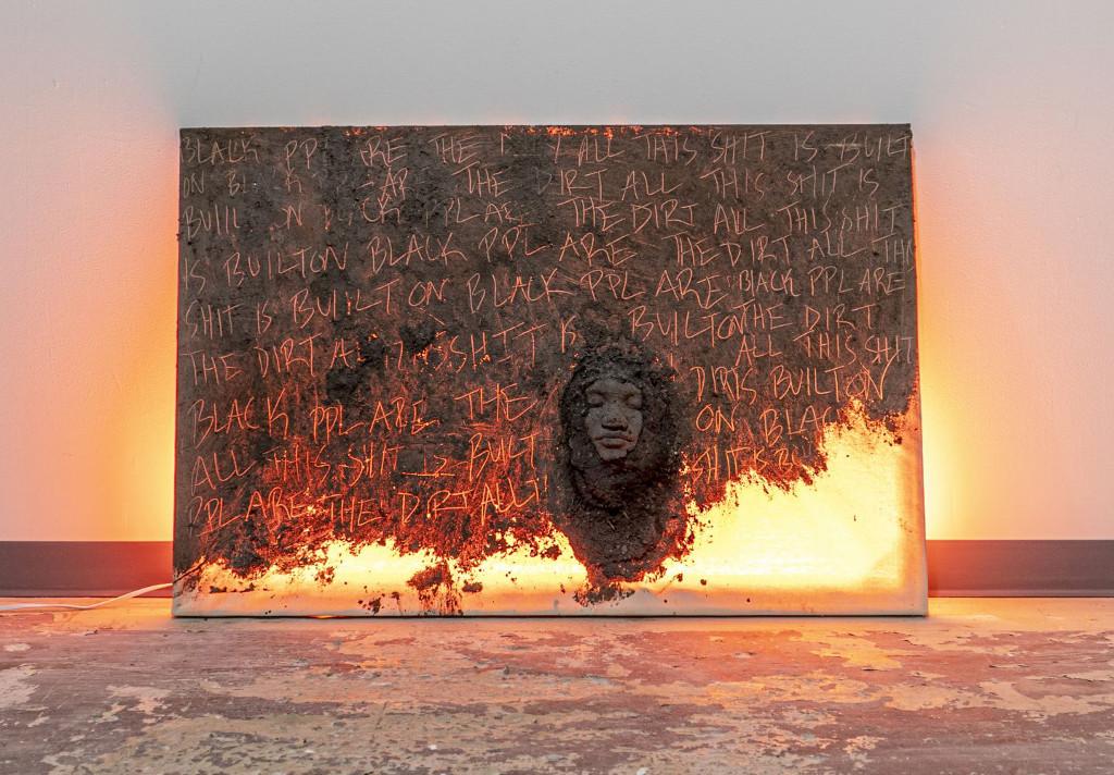 Das Bild zeigt eine künstlerische Installation. Sie besteht aus einer aufrecht stehenden Fläche, welche aus  Lehm oder ähnlichem Material zu besten scheint. In das Material sind Worte eingeritzt. Die Fläche ist von hinten beleuchtet oder scheint zu brennen, wodurch die Worte in der Oberfläche zu glühen scheinen. Rechts neben der Mitte der Fläche ist aus dem selben Material ein Kopf mit geschlossenen Augen angebracht. Im Vordergrund des Bildes ist ein unregelmäßiger lehmfarbener Fußboden zu sehen, im Hintergrund eine weiße Wand.