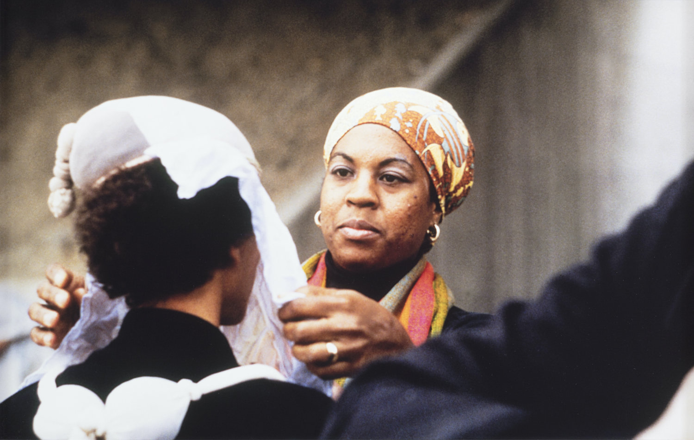 Senga Nengudi hängt ein Tuch über das Gesicht einer Frau.