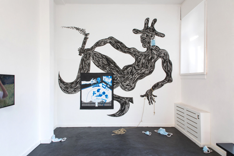 """Ausstellungsansicht """"Not Safe For Work"""". An die Wand ist ein rauchender Mann mit Hut gemalt, an seinem Ohr hängt eine Keramikmaske von Oliver-Selim Boualam von BNAG."""