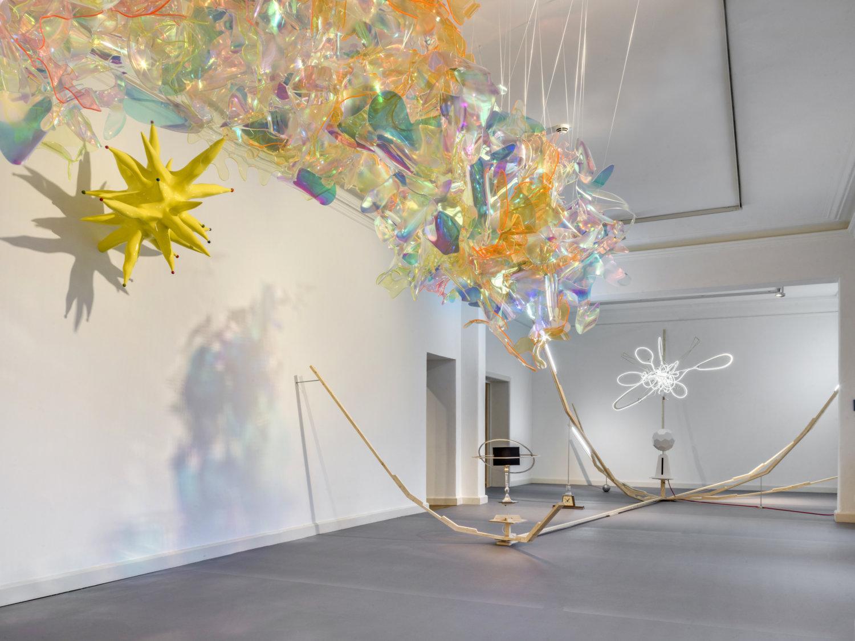 Installationsanicht in einem hellen Ausstellungsraum. Man sieht verschiedene bunte  Kunstobjekte, die sich im Raum befinden bzw. an der Wand hängen.