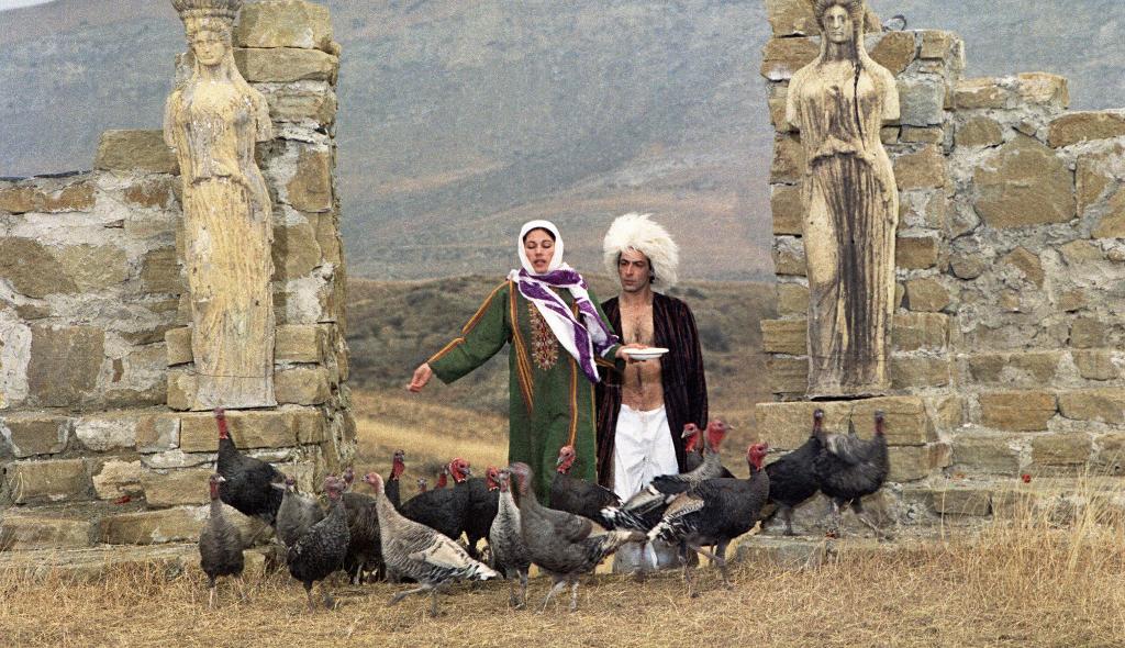 Das Bild zeigt einen Mann und eine Frau in einer Graslandschaft mit Ruine. Die Frau ist dabei, Hühner zu füttern, welche vor Ihnen laufen. Die Kleidung der Personen scheint nahöstlich, die Frau trägt einen grünen Kaftan und ein weiß-violettes Kopftuch, der Mann einen langen Mantel und eine Art Pelz-Turban.