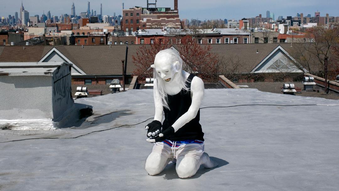 Ein weißer Zombie, der auf einem Hausdach in New York City kniet.