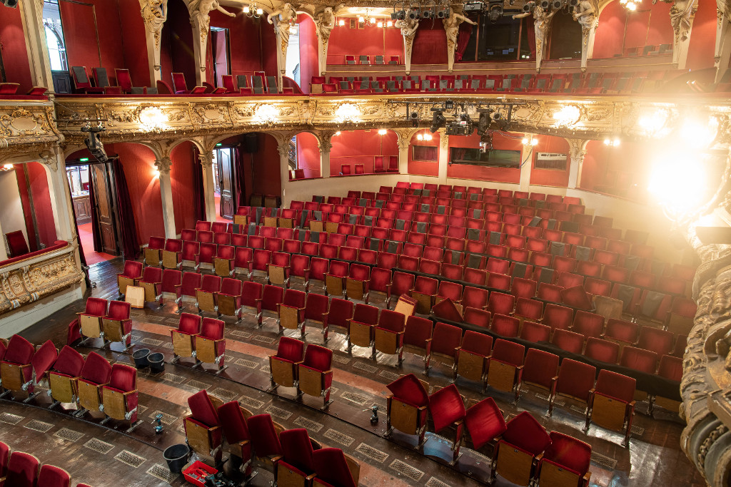 Das Bild zeigt den Innenraum eines Theaters aus Richtung der Bühne. Stühle und Wände sind durch eine starke dunkelrote Farbe grpägt, die Logen-Architektur mit Säulen ist in Sand- und Goldfarben gehalten. Es scheint sich um einen historischen Theaterbau zu handeln. Die Stuhlreihen im Vordergrund sind unvollständig eingebaut.
