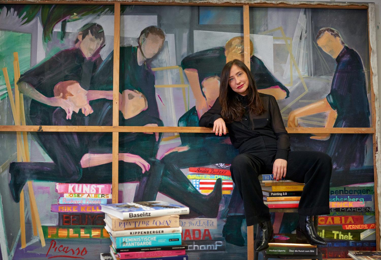 Die Malerin Egle Otto in ihrem Studio auf Kunstkatalogen sitzend