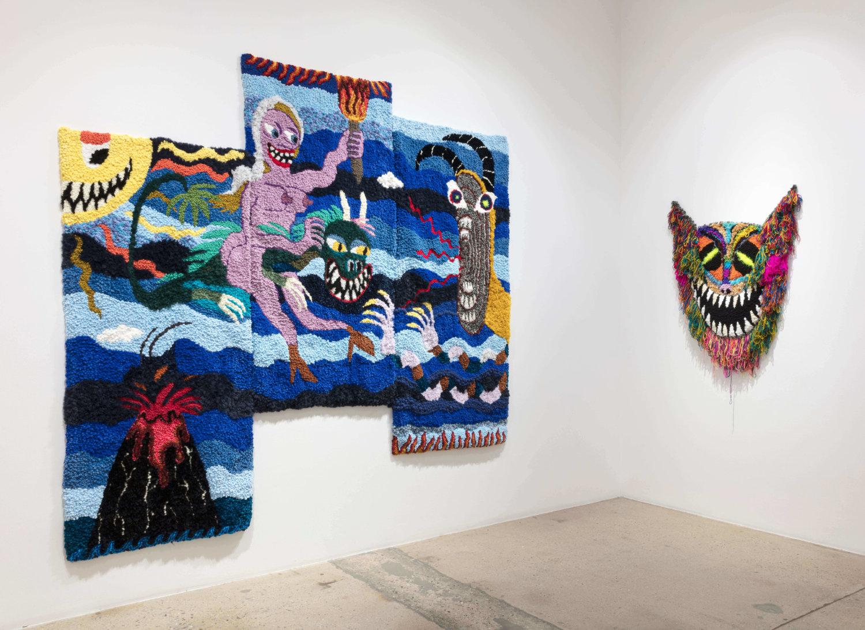 Wandteppiche von Hannah Epstein. Links reitet eine Frau mit Fackel in der Hand einen Drachen, rechts eine Art Drachenkopf.