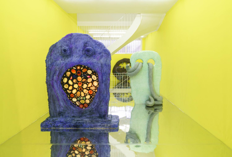 Blick in einen gelben Raum mit einer lilafarbenen und einer türkischen flachen Skulptur.